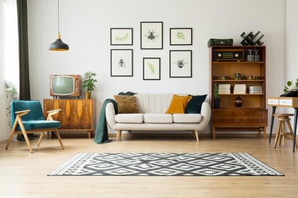 Salón decorado estilo vintage con muebles retro de madera, cojines en colores lisos mostaza, marrón y negro y alfombra estampada en blanco y negro.